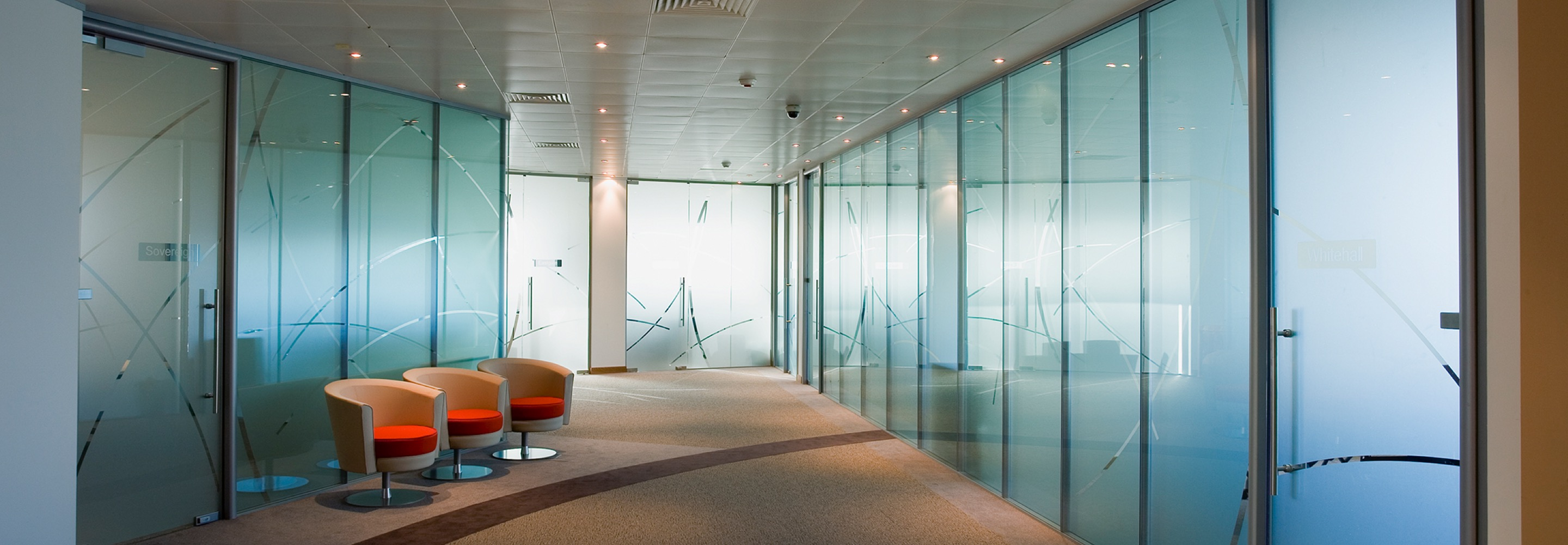 Corporate Interiors - glass partitions in modern office corridor