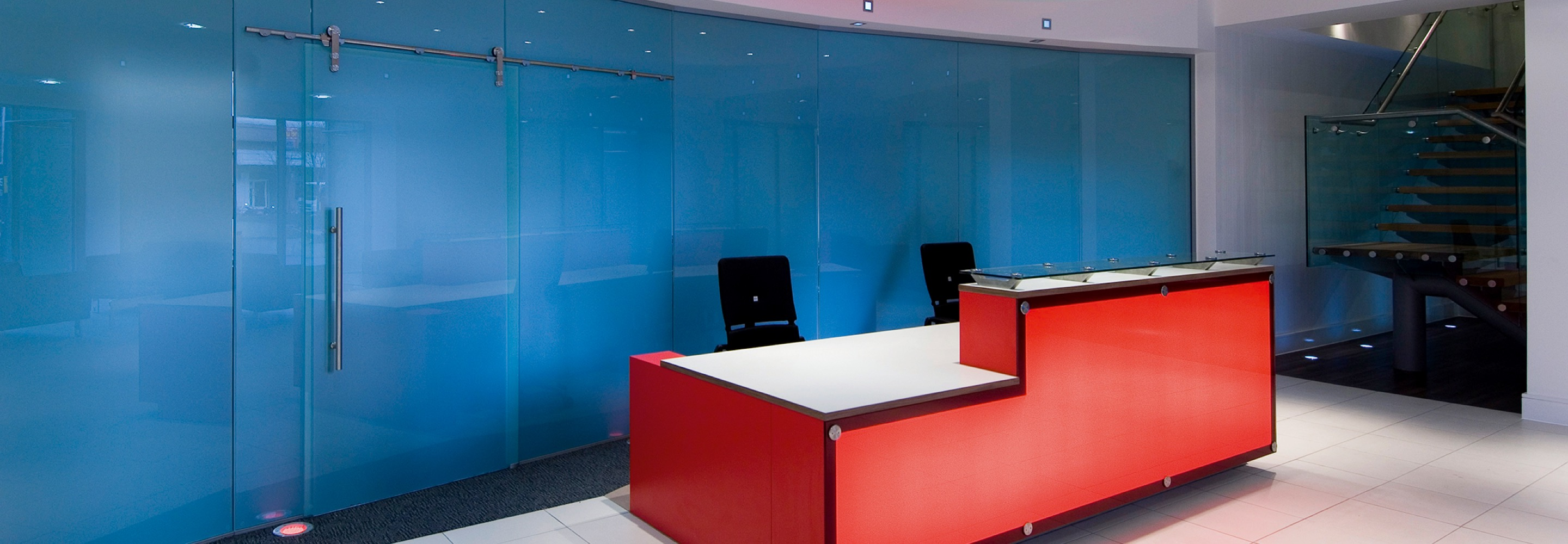 Corporate Interiors Design and Build - modern office reception with coloured glass design